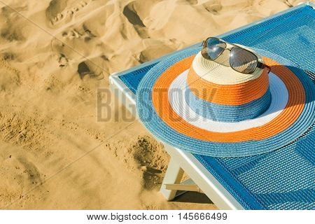 Colorful straw hat on a beach chair in the sand at the beach