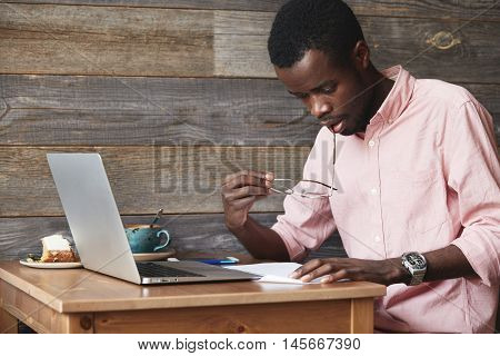 African Businessman In Formal Suit Having Stress While Working On Financial Report, Sitting In Front