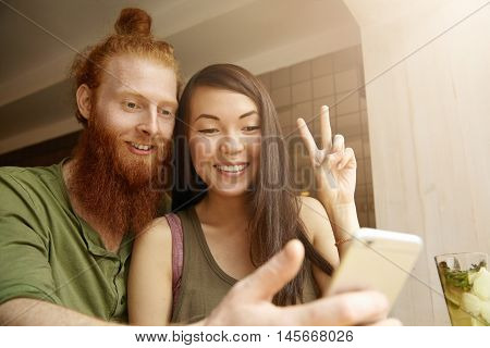 Portrait Of Hipster With Red Beard Using Generic Mobile Phone For Videoconferencing With Friends Onl
