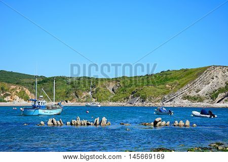 LULWORTH COVE, UNITED KINGDOM - JULY 19, 2016 - Boats moored in the bay Lulworth Cove Dorset England UK Western Europe, July 19, 2016.