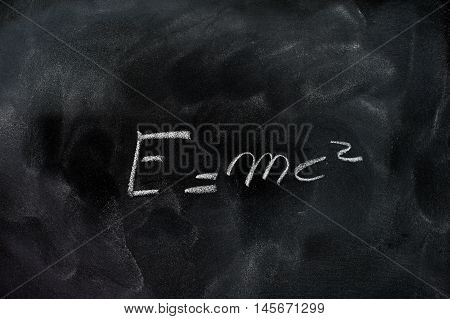 Einstein relativity formula e=mc2 white chalk drawing on dusty black school board poster