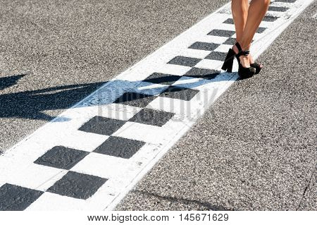 Woman sexy feet with high heels on motorsport chekered asphalt line