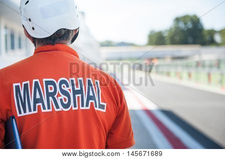 Motorsport track marshall orange racing bib close up with out of focus race track
