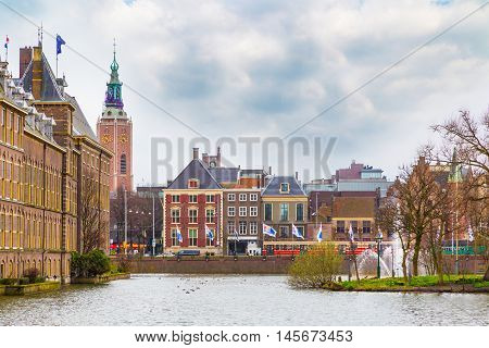 Hague, Netherlands - April 5, 2016: Street view with dutch houses, clock tower and lake in Hague, Holland