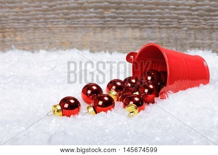 The bucket with scattered Christmas balls on snow