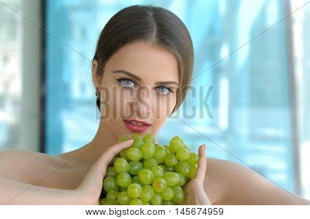 Girl Holding Grapes In Front Of Her Breasts