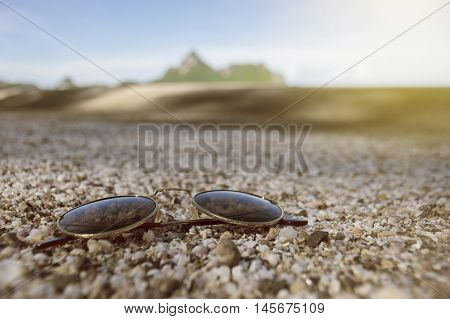 Vintage Sunglasses Put On A Lot Of Broken Small Corals, Scrap Of Sea Shell On The Sand With Blurred