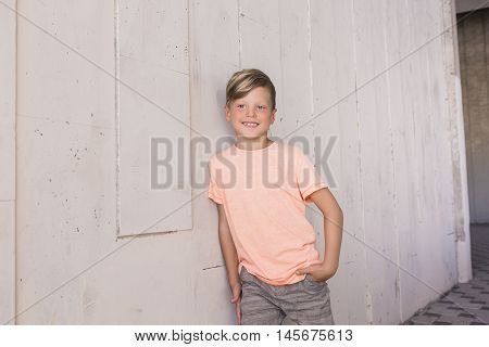 Stylish boy leaned on the wall and looks ahead with a smile . He has cool hair . Children's fashion .
