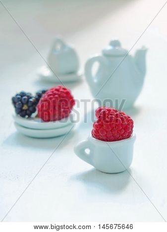 Tea time - fresh berries, white teacup and teapot on white background