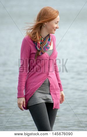 Red-haired woman walking in a pink blouse