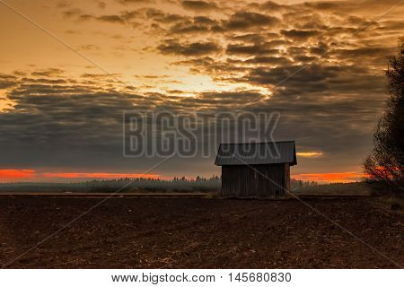 An old barn house on the early summer fields of the Northern Finland. The farmers are burning the fields using an old farming method called controlled burn.