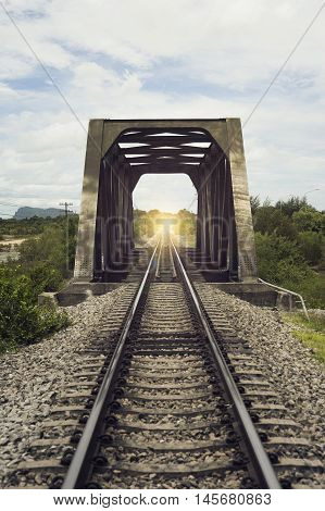 view of the length of railway and old steel bridge with green tree at left and right side of railway,filtered image,light effect added,selective focus,mean
