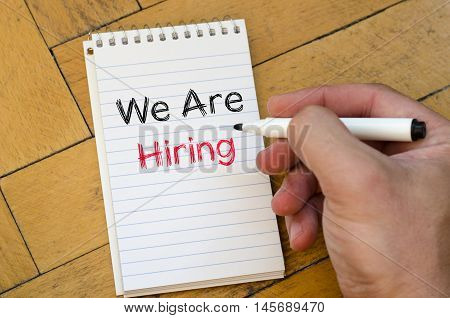 We are hiring text concept on notebook over wooden background