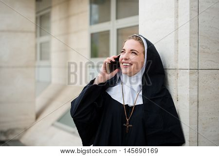 Young catholic nun calling phone - outdoors in street
