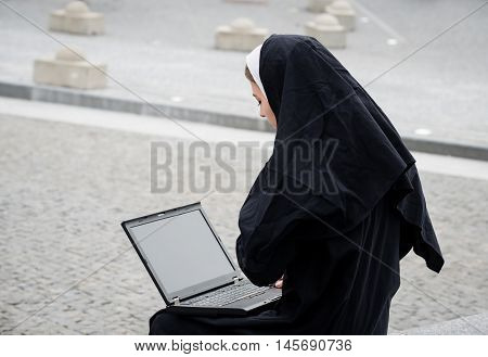 Catholic nun working on computer - outside in street
