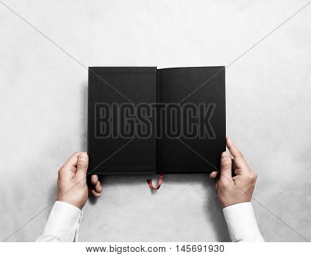 Hand holding blank opened book mock up with black half title. Person reading empty paperback mockup. Black notebook inside template. Publication design leafing man. Textbook spread with bookmark.