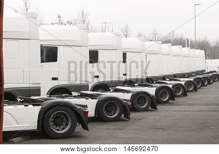long line of white trucks for sale on a parking place