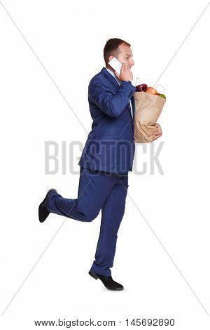 Smiling young businessman calls and runs with shopping paper bag full of groceries, vegetables and fruits, isolated at white background. Healthy food shopping. Full length portrait of hurrying buyer