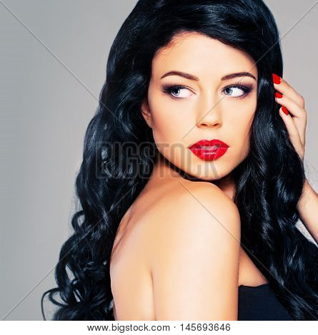 Glamorous Brunette Woman with Curly Hair and Red Lips Makeup