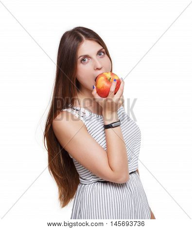 Beautiful long-haired young woman eats big ripe red apple. Female portrait isolated on white background. Girl bites fruit, hand with fitness tracker bracelet, healthy food and diet concept.