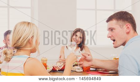 Surprised man and blond woman at dinner table, party for friends indoors at cafe or home. Friendship, relationship, relax at holidays and week-end. People sitting at table, saying toast