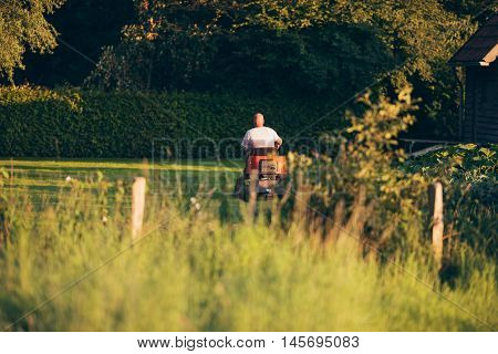 Rear View Of Man On Tractor Mower In Garden.