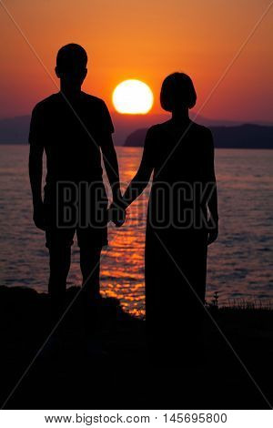 Couple in Love. Silhouettes of Man and Woman during Sunset