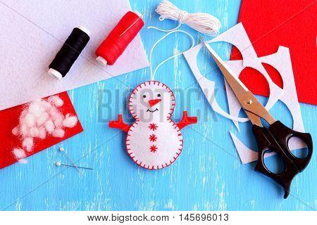 Fun felt Christmas snowman ornament, scissors, thread, needle, pins, cord, felt pieces and scraps on wooden background. How to make a Christmas snowman ornament. Step. Handmade felt crafts. Top view