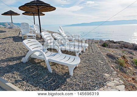 Pebble beach, chaise-longues and umbrellas in Istria, Croatian coast