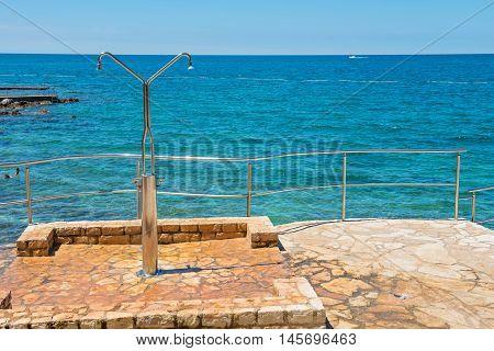 Shower on the rocky beach in Istria, Croatian coast