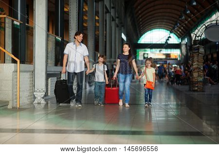 Father mother and two children pass the waiting room at the station. Parents hold children's hands and roll the suitcases. Family in good mood. In the hall many passengers.