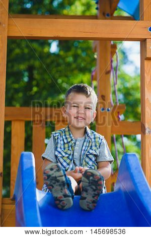 Smiling kid having fun at playground. Child playing outdoors in summer. Boy sitting on children's slide.