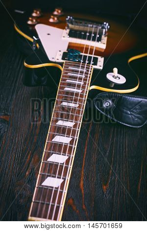 Electric guitar fretboard on wooden table close up