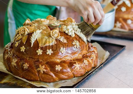Hand with brush touches bread. Loaf on oven tray. Freshly cooked wedding bread. Food for guests of ceremony.