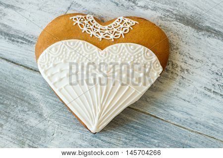 Wedding dress heart biscuit. Frosted cookie on wooden surface. Make treats for special occasion. Taste of new life.