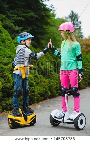 Happy kids standing on hoverboards and show thumbs up outdoor