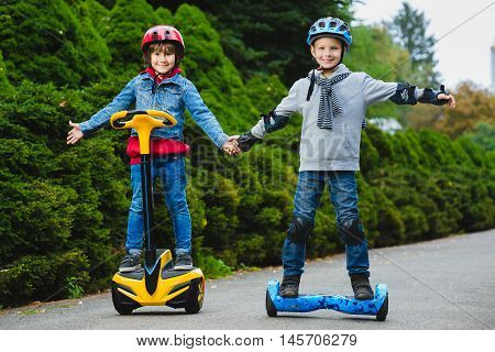 Happy boys riding on hoverboards or gyroscooters outdoor.