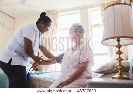 Female nurse doing blood pressure measurement of a senior woman patient. Doctor checking blood pressure of an elderly woman at old age home.