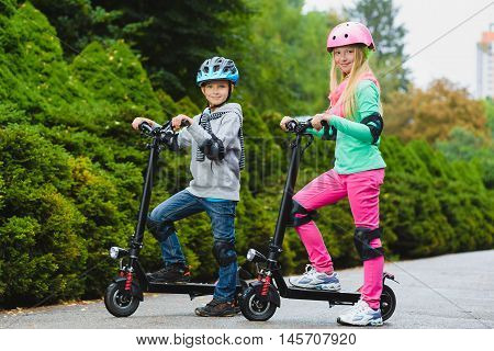 Happy kids standing on electric scooter outdoor.