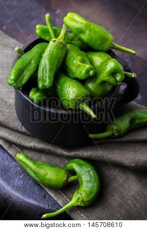 Food and drink, still life, moody concept. Raw green peppers pimientos de padron traditional spanish tapas on a black rusty table. Selective focus