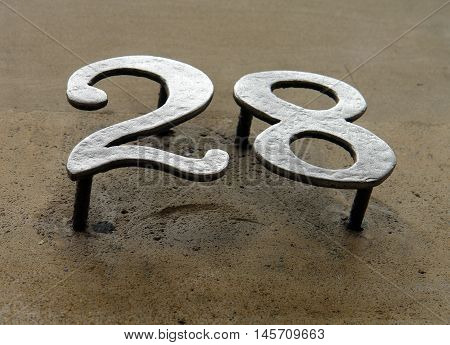 iron house number on the stone wall 28 the number of copper