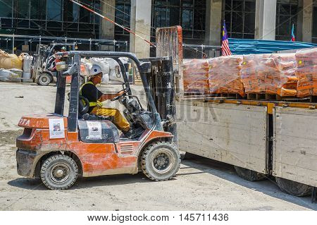 Kota Kinabalu,Sabah-Aug 30,2016:Unidentified worker with forklift stacking pallets with cement packs from lorry at Kota Kinabalu,Sabah,Borneo on 30th Aug 2016.
