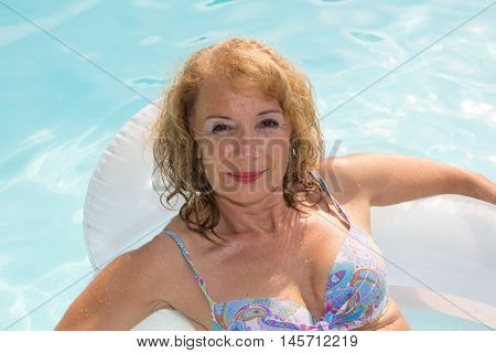 summer vacations image with adult midlife woman relaxing in a beautiful lake