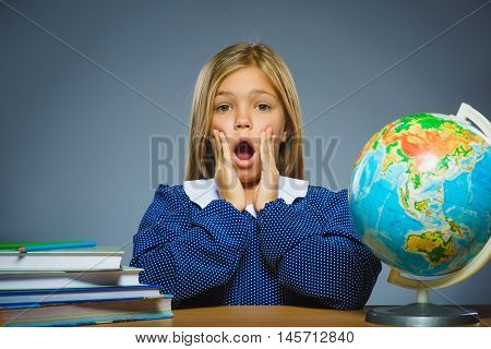 school concept. girl with astonished or doubt expression sitting at desk.