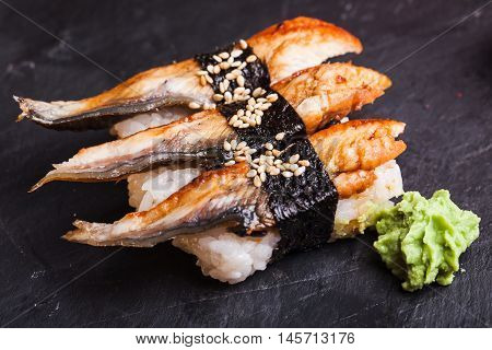 Close-up of Unagi sushi with eel and wasabi on a black slate background