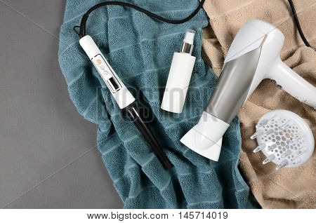 Hairstyling Tools (white Hairdryer, Hairspray, Cone Curling Wand) On Beige And Greenish-blue Towels.