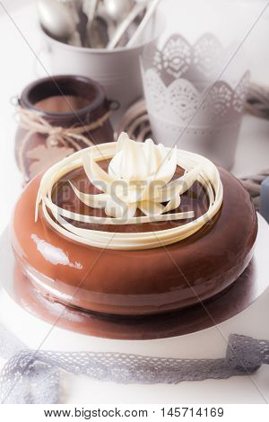 Round french chocolate cake covered with mirror chocolate icing and decorate with white chocolate