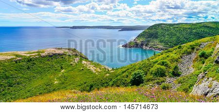 Sunny summer day over rocky coastline cliffs of Canadian National Historic site  Fort Amherst, St John's Newfoundland.  Cape Spear in background, people in distance hiking along the Cabot trail.