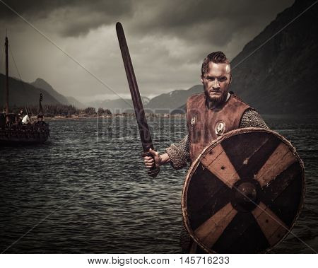 Serious viking warrior in the attack, standing along the shore with Drakkar and mountains on the background.