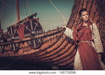 Beautiful viking woman standing near Drakkar on the seashore.